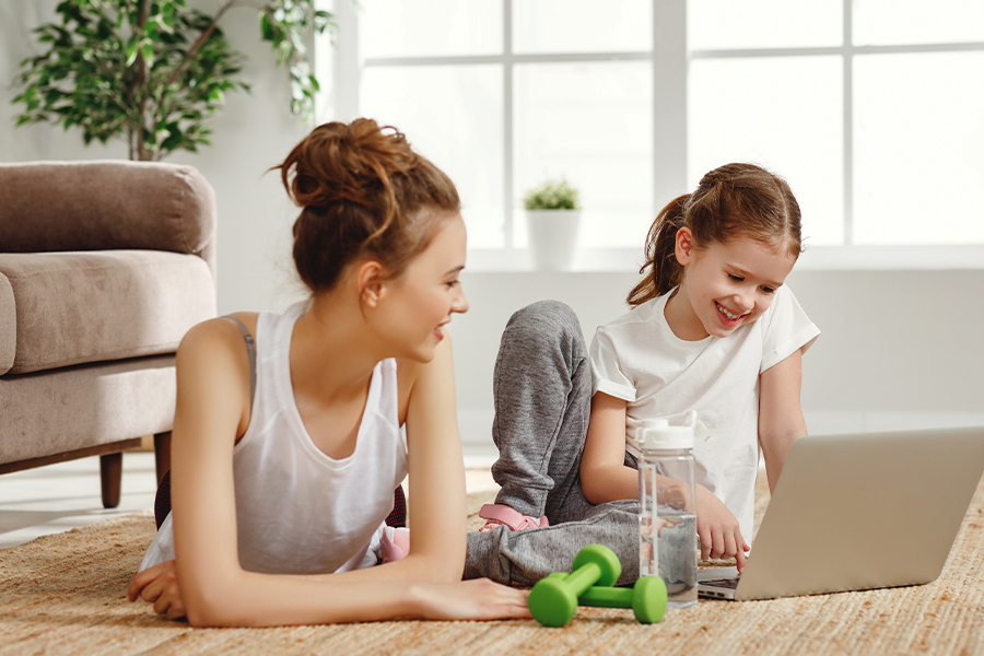 Employee Benefits - Cheerful Mom and Daughter Using Laptop While Exercising at Home